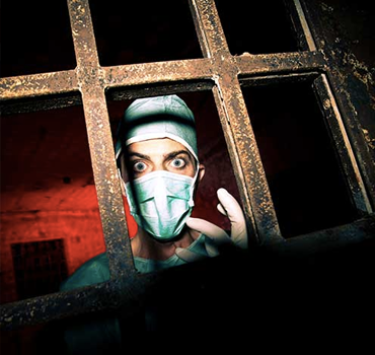 Photograph of a psycho surgeon staring at the camera through a prison gate